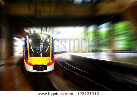 Train approaching station platform with blur motion