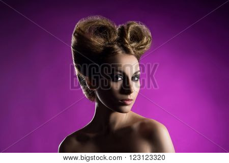 Portrait of a beautiful woman with a bizarre haircut over bright background