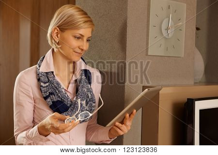 Blonde woman holding tablet, reading at home.
