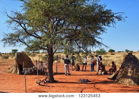 KALAHARI NAMIBIA - JAN 24 2016: Tourists visit bushmen tribe village. The San people also known as Bushmen are members of various indigenous hunter-gatherer peoples of Southern Africa
