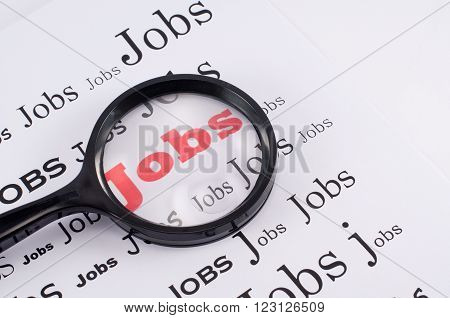 Job search concept with magnifying glass highlighting the word Job