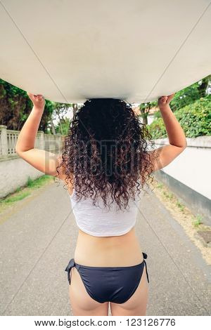 Back view of curly brunette girl with white top and black bikini holding surfboard over head on the street. Summer lifestyle concept.