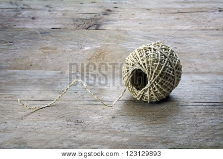 Ball of string with texture and strands on a rustic gray wooden background copy space
