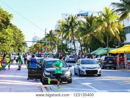 MIAMI BEACH, USA - MAY 9, 2015: Cars driving and parking people walking by or running street cafes with sunshades on the side of the Ocean Drive.