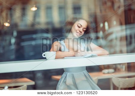 do everything with inspiration. Cheerful content  beautiful girl sitting at the table and making notes while feeling joy