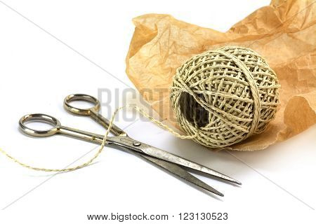 wrapping material ball of string paper and scissors isolated with shadow on white as a corner background selected focus narrow depth of field