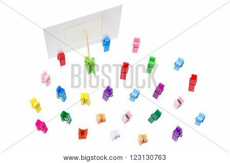 Green clothespin shows toothpick on white border Group of colorful clothespins