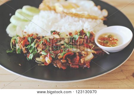 Thai stir-fried pork and basil served with rice and fried egg / Pad kra Prao