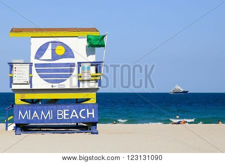 MIAMI BEACH, USA - MAY 9, 2015: A section of the beach with a lifeguard station and some people sunbathing or swimming, a yacht on the ocean in the back.