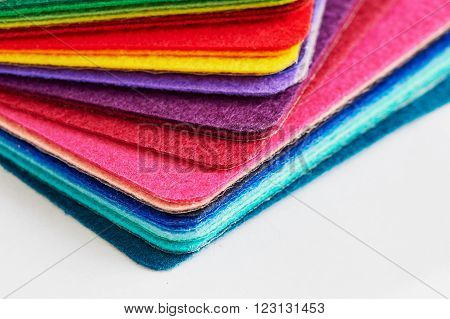 Felt fabric sheets in various colors piled up in a stack.