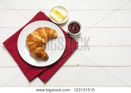 continental breakfast with croissant and jam on a red napkin on a white painted wooden background view from above generous copy space