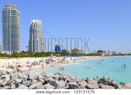 MIAMI BEACH, USA - MAY 9, 2015: Scene of the crowded beach. People having fun sunbathing and swimming in the shallow water. Skyline in the back.