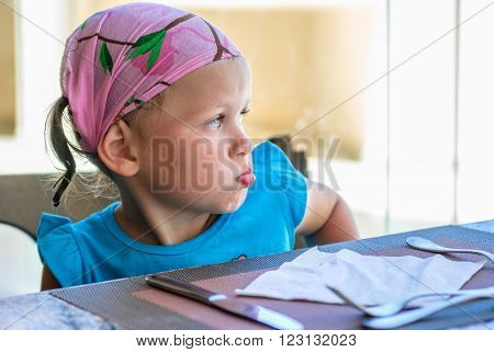 Girl in bandana looking out the window his cheeks puffed out and sitting at a table on which lay cutlery and napkin