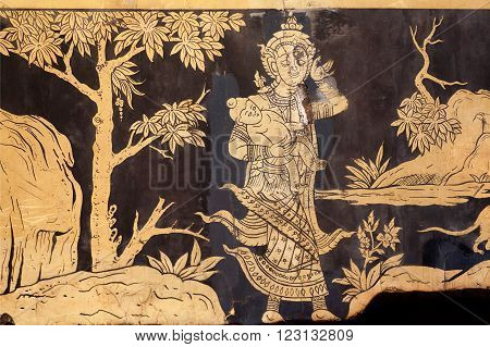 BANGKOK, THAILAND - FEB 14: Mother holding a child in forest on wall with vintage murals of Wat Pho temple on February 14, 2015. Wat Pho is a Buddhist temple complex founded in 16th century