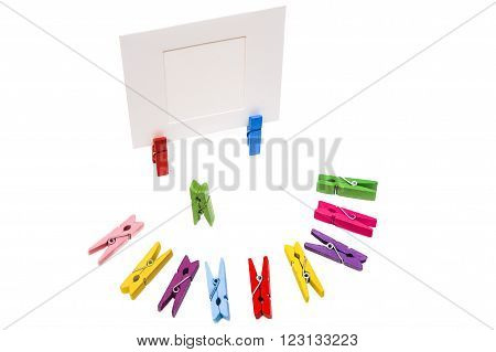 Green clothespin stands in the center. Colored pegs lie in a semicircle. Two clothespins holding white frame