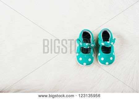 Green baby girl shoes with white dots. On a white fur carpet.