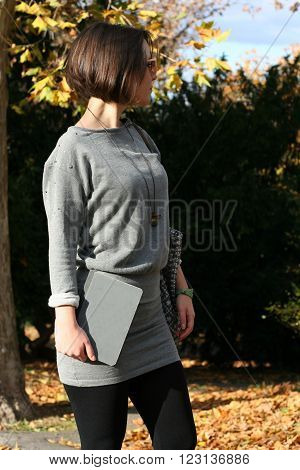 Bob-haired girl in grey dress stanging looking to the side and holding notepad in autumn park full of colored leaves and trees.