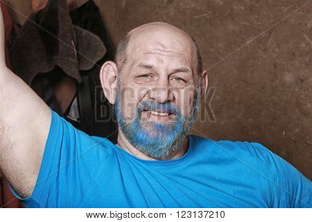 close-up portrait of an adult man with a blue beard and mustache in the dressing room
