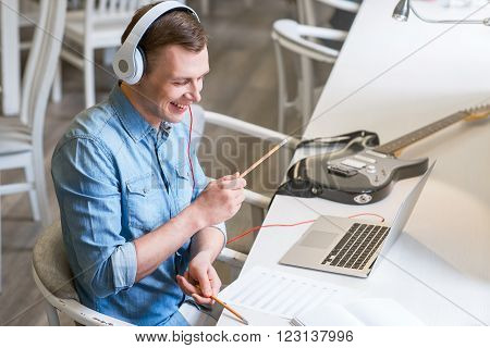 Like a real drummer.  Cheerful delighted handsome guy sitting at the table a pretending to drum while listening to music
