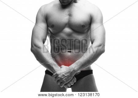 Man with pain in the prostate. Muscular male body. Handsome bodybuilder posing in studio. Isolated on white background with red dot. Black and white photography