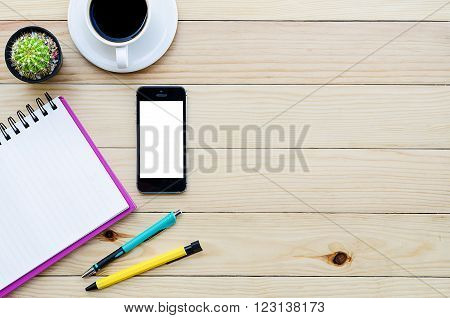 Office desk table with smartphone coffee cup pen pencil and notebook.Top view with copy space