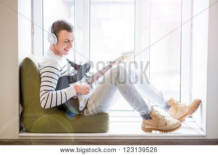 Enticed in music. Cheerful delighted handsome guy sitting on the window sill and holding the guitar while playing it