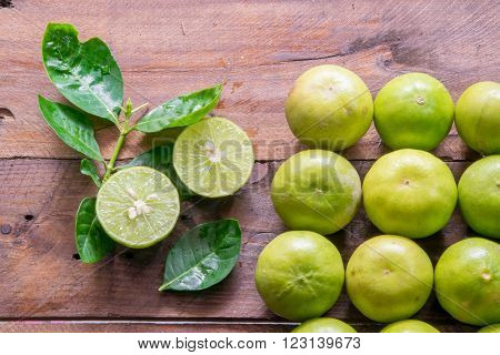 Lemons green with leaves on hard wood