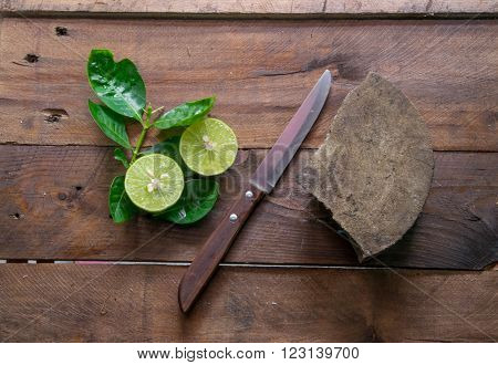 Green lemons and leaves  with knife On wood