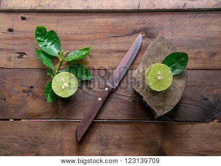 lemons with knife on wood (focus lemon on block)