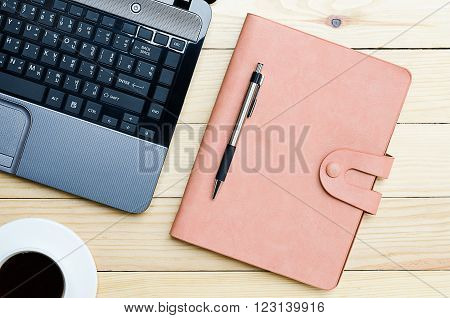 Leather notebook with pen cup of coffee and labtop on office desk.Top view