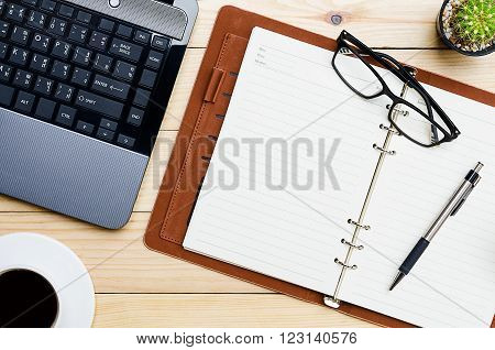 Blank leather notebook with pen glasses labtop and cup of coffee on office desk.Top view