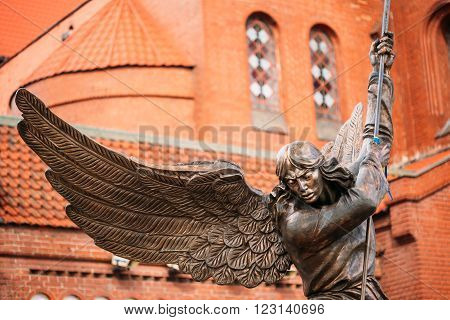 Statue Of Archangel Michael Near Red Catholic Church Of St. Simon And St. Helena On Independence Square In Minsk, Belarus