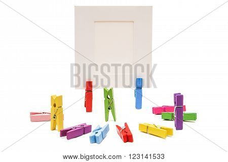 Three clothespins standing others are semicircular. Two clothespins holding white frame behind the