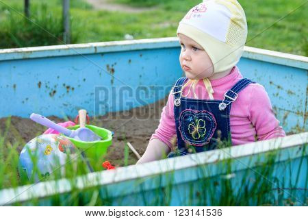 Little girl sits in a sandbox with toys: bucket shovel ball