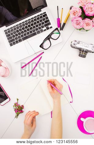 The female hands writing against fashion woman objects on white. Concept of female mockup and comfortable  female workplace