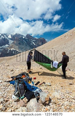 Group of Alpine Climbers Working on setting up Camping Tents with Many Gear Dropped Around and Rocky Mountain Moraine on Background