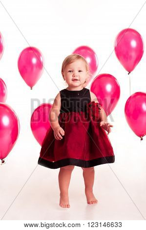Laughing baby girl 2-3 year old having fun with pink balloons in room over white. Looking at camera. Birthday party. Celebration.