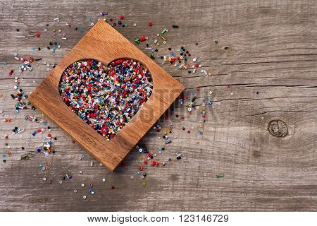 Heart from colourful beads in wooden heart-shaped box on wooden background