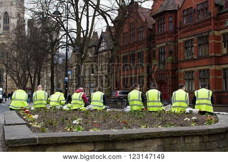 YORK, UK - MARCH 24. Workmen in hi-visibility clothing taking a break from construction and sitting outside in the City of York.