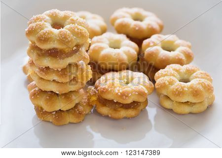 Sweet crispy pineapple biscuit and cookie scatter over with sweet sugar in white plain plate ready to eat/ Sweet crispy pineapple biscuit with sugar