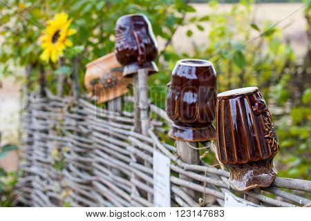 Brown clay pots on the wicker fence