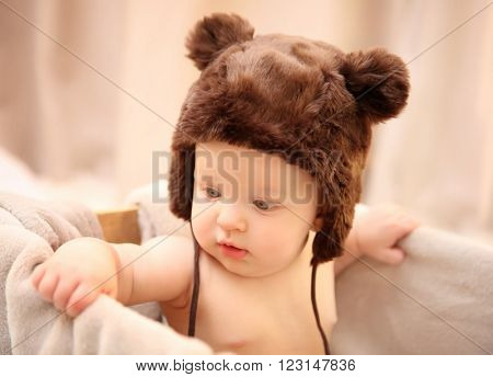 Adorable baby in brown knitted hat sitting in wooden box with soft plaid, close up