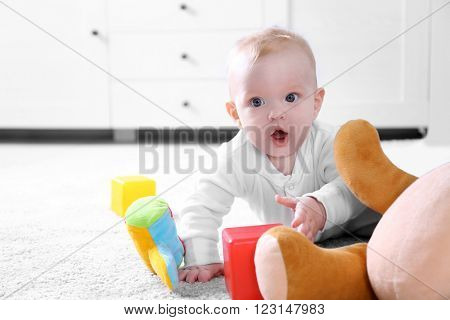 Cute baby boy playing with toys on white carpet at home