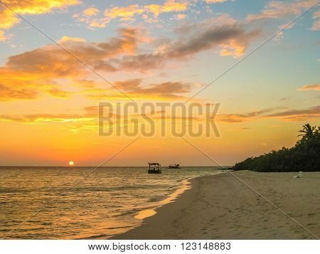 Maldives background. Sunset over the tropical sea and coral beach with colorful clouds in the sky. Boats on the horizon in heavenly atoll of peace and relaxation. North Male Atoll Asdu, Indian Ocean.