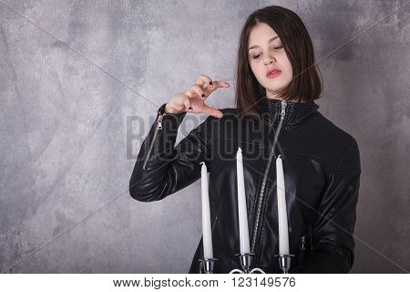Teen Girl In Leather Jacket With A Candelabra In Hand.