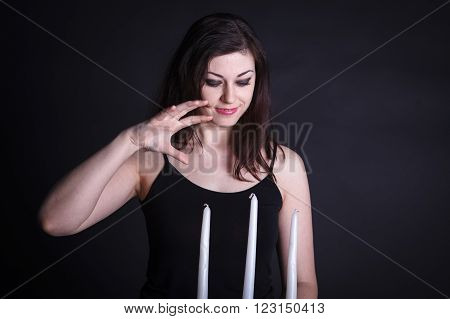 Beautiful Woman On A Dark Background With The Candlestick In Hands