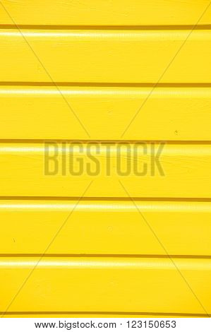Closeup of bright empty wooden clapboard textured siding painted in yellow color with horizontal lines and nobody copy space vertical picture