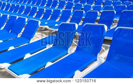 Many empty canvas blue beach hotel chaise-longue chairs standing in row on sand coast outdoor sunny day with no people, horizontal picture