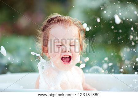 Laughing baby girl having fun washing in bath outdoors. Cheerful. Happiness. Childhood.