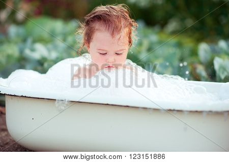Cute baby girl bathing outdoors. Childhood. Bubble bath. Washing.